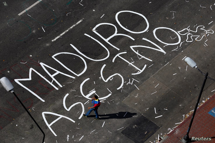 An opposition supporter walks past a words painted on a blocked street, reading 'Maduro murderer', at Altamira Square in Caracas, Feb. 21, 2014.