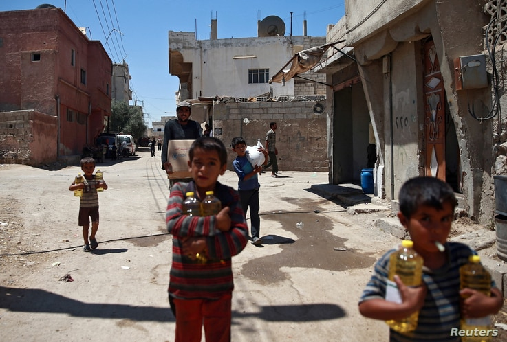 FILE - Syrian children and a man are seen carrying food aid in Douma, near Damascus, Syria, Aug. 6, 2017.