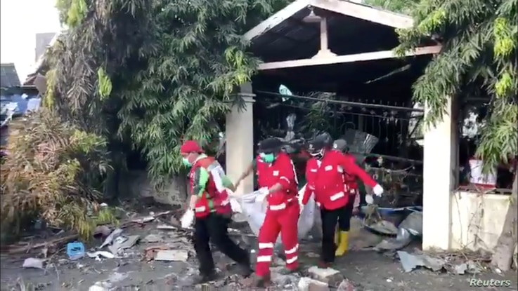 Bodies are carried out of a house on Talise beach, Central Sulawesi, Indonesia, Oct. 3, 2018, in this still image obtained from a social media video.