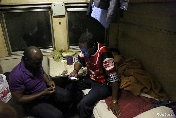 Gilbert Mthinzima Ndlovu (R), a veteran of Zimbabwe's 1970s independence war and a security guard at the National Railways of Zimbabwe (NRZ) for 35 years, chats to his colleague in a carriage during an overnight train journey from Harare to Bulawayo,...