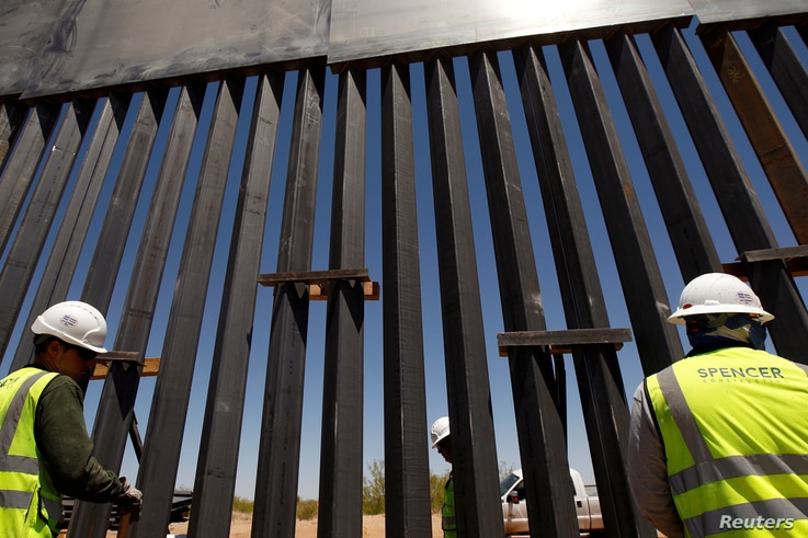 FILE - Construction workers check a new section of bollard wall in Santa Teresa, N.M., as seen from the Mexican side of the border in San Jeronimo, on the outskirts of Ciudad Juarez, Mexico,