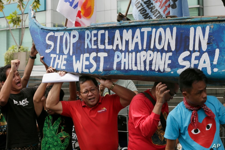 Protesters carry a boat painted with slogans during a rally outside the Chinese Consulate in Makati city, east of Manila, Philippines, to protest China's reclamations of disputed islands off South China Sea, July 3, 2015.