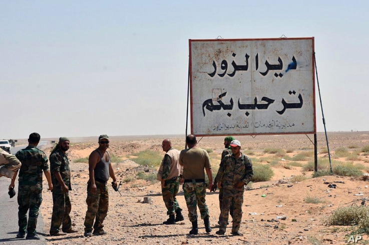 "This photo released Sept 3, 2017 by the Syrian official news agency SANA, shows Syrian troops and pro-government gunmen standing next to a placard in Arabic which reads, ""Deir el-Zour welcomes you,"" in the eastern city of Deir el-Zour, Syria."