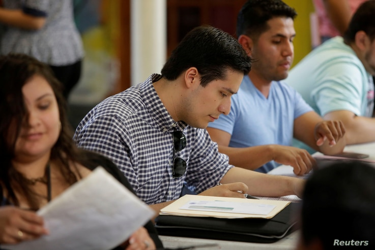 Ernesto Delgado, center, a Deferred Action for Childhood Arrivals (DACA) recipient, fills out his renewal application during the immigration ministry at Lincoln Methodist Church in Chicago, Sept. 10, 2017. DACA recipients gathered to fill out applica...