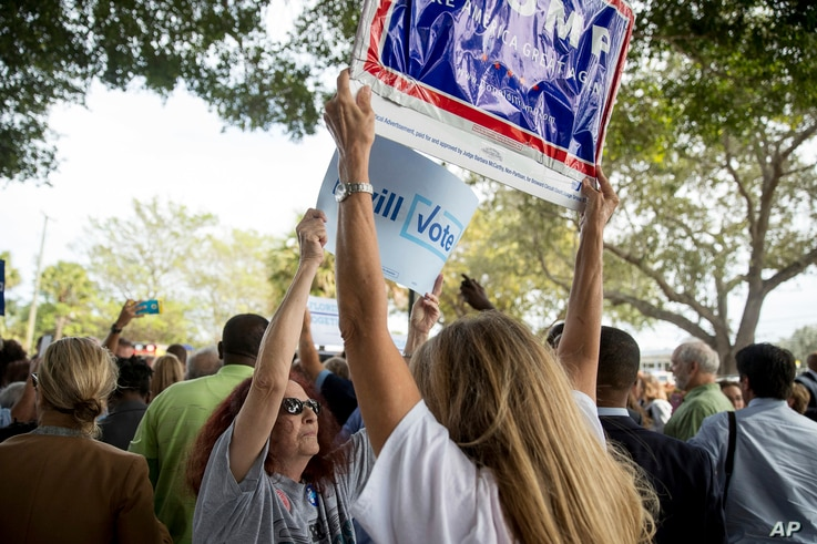 A supporter of Democratic presidential candidate Hillary Clinton attempts to block a Republican presidential candidate Donald Trump supporter from waving a sign as Clinton greets supporters outside an early voting station in Pompano Beach, Fla., Oct....