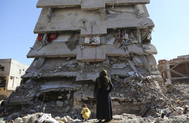 A woman looks at a building, which was damaged during the security operations and clashes between Turkish security forces and Kurdish militants, in the southeastern town of Cizre in Sirnak province, Turkey, March 2, 2016.