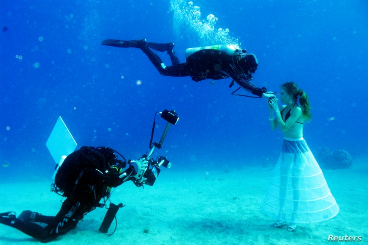 A model opens her mouth to breathe from a scuba tank as Israeli photographer Johannes Felten (L) takes pictures during an underwater photo shoot in the Red Sea in the resort city of Eilat, Oct. 22, 2013.