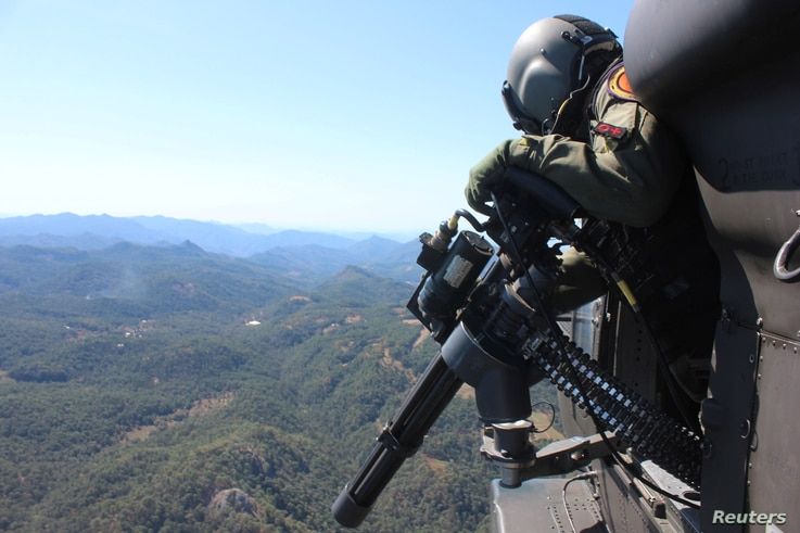 A soldier flies in a helicopter as he patrols at a poppy plantation used to make heroin during a military operation in the state of Sinaloa, Mexico, March 18, 2017.