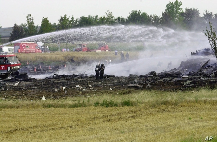 Firefighters spray water on the debris of the plane that crashed on a hotel after an Air France Concorde en route to New York City crashed in Gonesse, outside Paris, shortly after take off, July 25, 2000, slamming into a hotel.