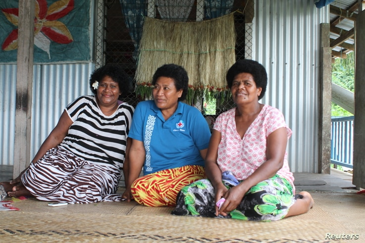 Villager Biusalia Tevita (C) poses for photo in her home for the Thomson Reuters Foundation with village nurse Seruwaia Kula (L), and a neighbor at Wailotua Village No. 1, an inland community of about 200 people that is prone to flooding, cyclones an...