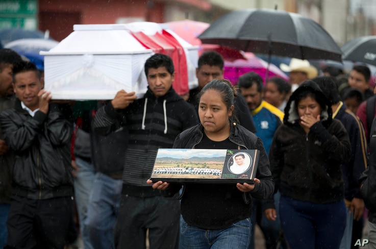 FILE - A young woman walks with a photo of Jesus Cadena in his funeral procession in Nochixtlan, in Oaxaca state, Mexico, June 21, 2016. It was two days after he was killed in a clash between police and striking teachers.