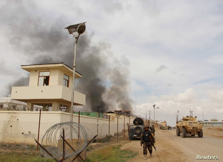 A member of the Afghan security forces walks as smoke billows from a building after a Taliban attack in Gereshk district of Helmand province, Afghanistan, March 9, 2016.