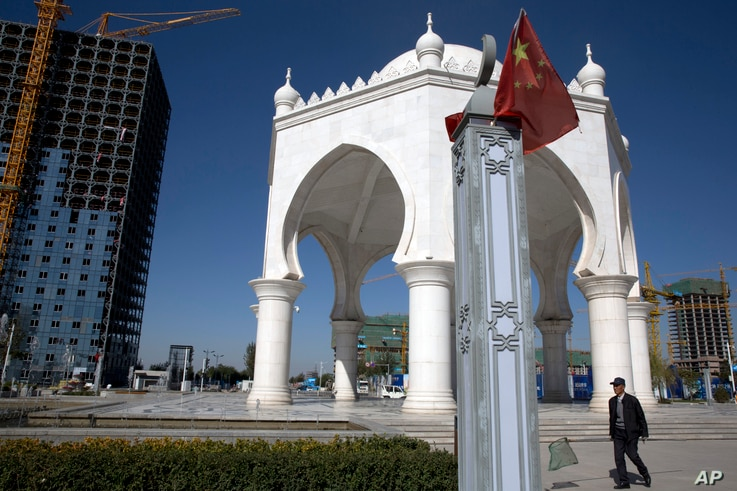 FILE - A man walks past a pavilion with Islamic architectural features in Yinchuan in northwestern China's Ningxia Hui autonomous region, Oct. 8, 2015.