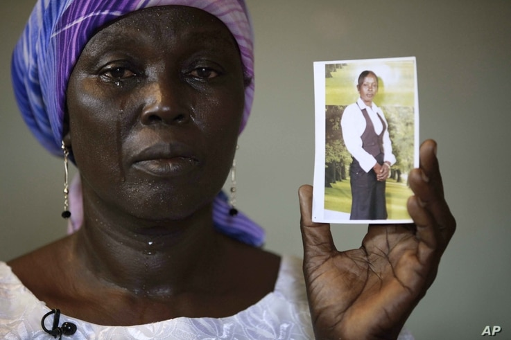 FILE - Martha Mark, mother of kidnapped schoolgirl Monica Mark, cries as she displays her photo in the family's house in Chibok, Nigeria, May 19, 2014