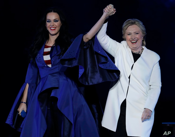 Katy Perry, left, holds hands with Democratic presidential nominee Hillary Clinton during a concert at the Mann Center for the Performing Arts, Nov. 5, 2016, in Philadelphia.