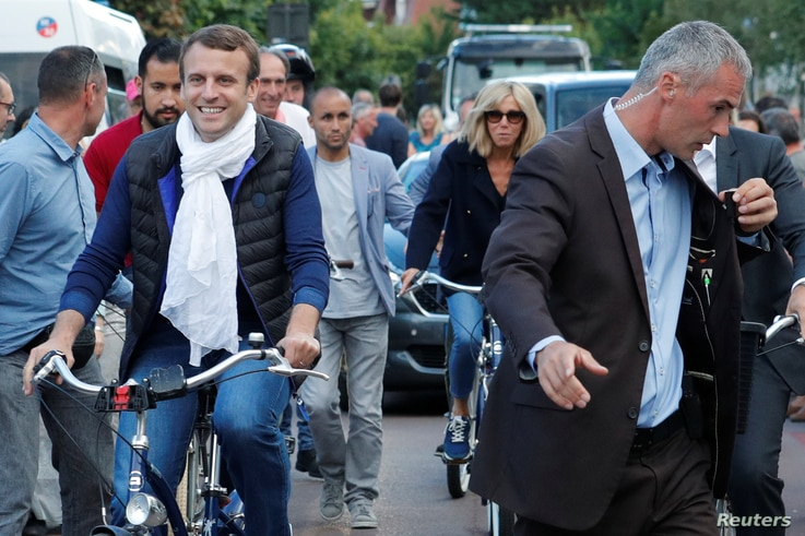French President Emmanuel Macron and his wife Brigitte Trogneux (center) leave their home on bicycles in Le Touquet, France, on the eve of the first round of the parliamentary election, June 10, 2017.