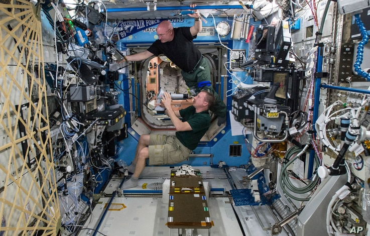 FILE - In this April 9, 2015, file photo made available by NASA, astronauts Terry Virts, bottom, and Scott Kelly perform eye exams in the Destiny Laboratory of the International Space Station as part of ongoing studies on vision health in microgravit...