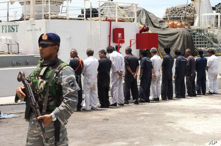FILE - Navy personnel stand guard as the crew of Silver Sea 2, a Thai-owned cargo ship which was seized by Indonesian authorities last August, are lined up during a media conference at the port of Sabang, Aceh province, Indonesia, Sept. 25, 2015.