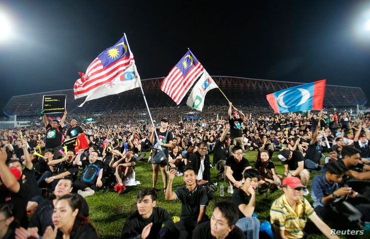 Opposition supporters wave flags as they attend a rally in protest of Sunday's election results at a stadium in Kelana Jaya, Malaysia, May 8, 2013.