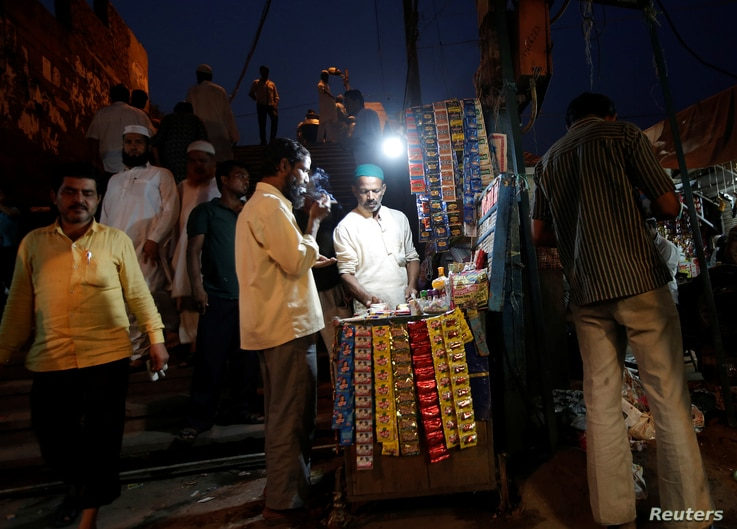 A man lights a cigarette at a roadside stall in the old quarters of Delhi, India, May 30, 2017.