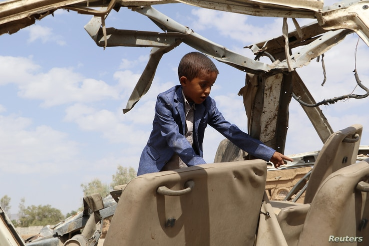 FILE - Hafidh Abdullah al-Khawlani, who survived a Saudi-led air strike stands on the wreckage of a bus destroyed by the strike in Saada, Yemen Sept. 4, 2018.