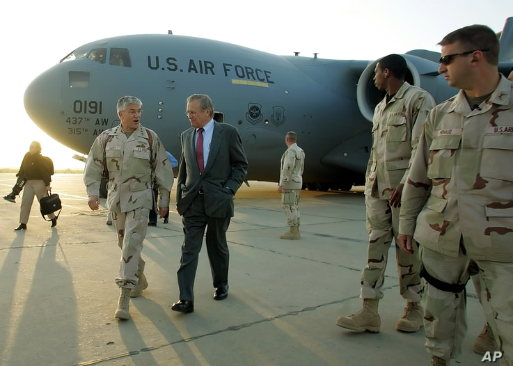 US Defense Secretary Donal Rumsfeld, center, speaks with US Army General George Casey, second from left,  upon arriving at Baghgad International Airport, April 26, 2006.