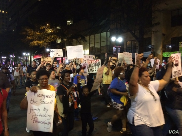 "Protesters, marching for a fourth night after an African-American man was shot to death by police on Tuesday, chant, ""Hands up, don't shoot,"" as they walk, in Charlotte, North Carolina, Sept. 23, 2016."