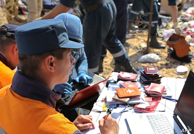 Russian rescuer checking passports collected from the wreckage of a A321 Russian airliner in Wadi al-Zolomat, a mountainous area of Egypt's Sinai Peninsula. (Russian Emergency Ministry Handout photo)