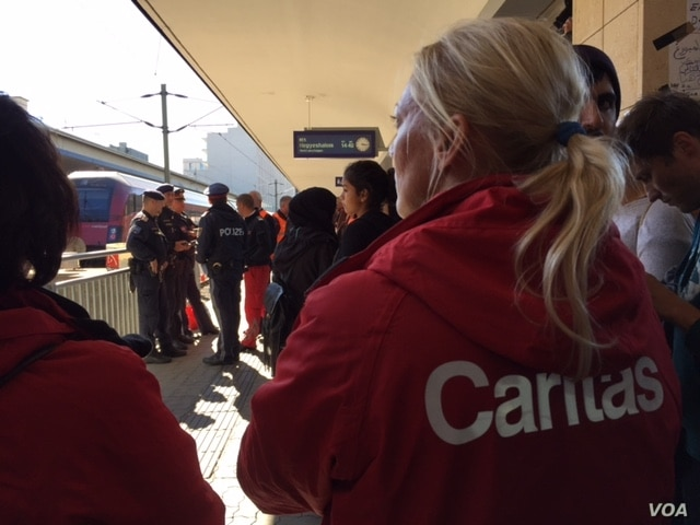Austrian relief workers await thousands of refugees arriving at the Vienna train station from the Hungarian border, Sept. 6, 2015.
