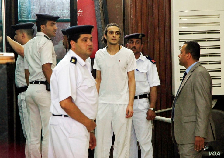 FILE - Egyptian photojournalist Mahmoud Abu Zied, known by his nickname Shawkan, center, appears before a judge for the first time after spending more than 600 days in prison in Cairo, May 14, 2015.