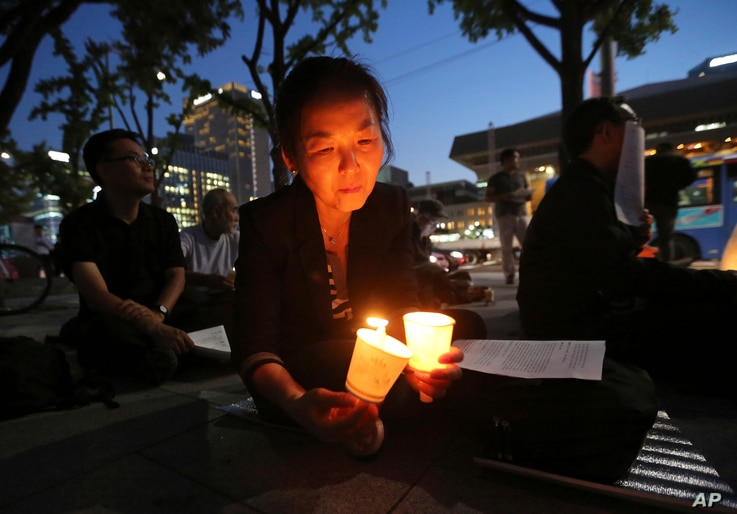 A woman lights candles during a service for peace on the Korean Peninsula near the U.S. Embassy in Seoul, South Korea, Aug. 31, 2017. The United States flew some of its most advanced warplanes in bombing drills with ally South Korea on Aug. 31, a cle...