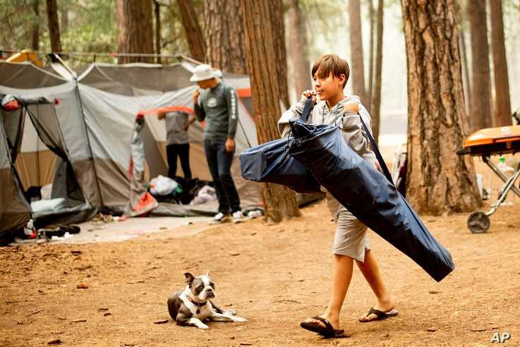 River Martinez, 10, breaks camp at the Upper Pines Campground in Yosemite National Park, Calif., July 25, 2018. Martinez's family, visiting from Los Angeles, had to cut their stay short as portions of Yosemite closed to allow crews to battle the Ferg...