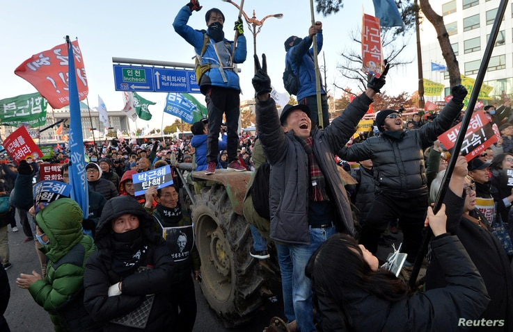 """People react after impeachment vote on South Korean President Park Geun-hye was passed, in front of the National Assembly in Seoul, South Korea, Dec. 9, 2016. The sign reads """"Arrest Park Geun-hye."""""""