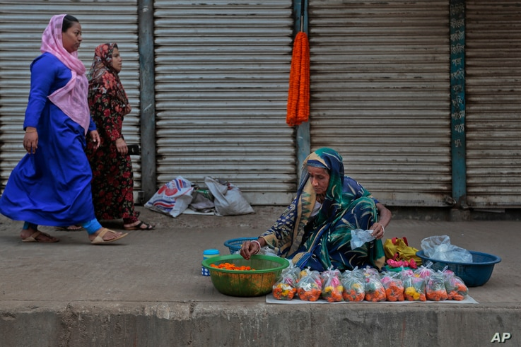 Two Bangladeshi Muslim women walk past a Hindu woman selling flowers by a roadside in Dhaka, Bangladesh, March 28, 2016. Hindus, along with Buddhists, represent the main minority groups in the majority Muslim country.