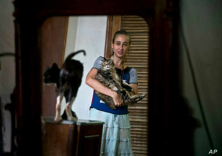 Grettel Montes de Oca Valdes, a professional dancer and founder of the group Cubans in Defense of Animals poses with cats in her home in Havana, Cuba, April. 4, 2019. A group of animal-lovers will march down one of Havana's main thoroughfares Sunda...