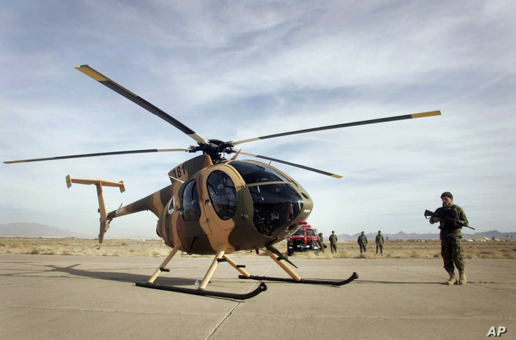 An Afghan soldier stands guard near a donated helicopter by U.S. to Afghan air force in Shindand district of Herat province, west of Kabul, Afghanistan, Saturday, Dec. 10, 2011. U.S. donated 18 helicopters and aircrafts including C-182, C-208 and Mi-...