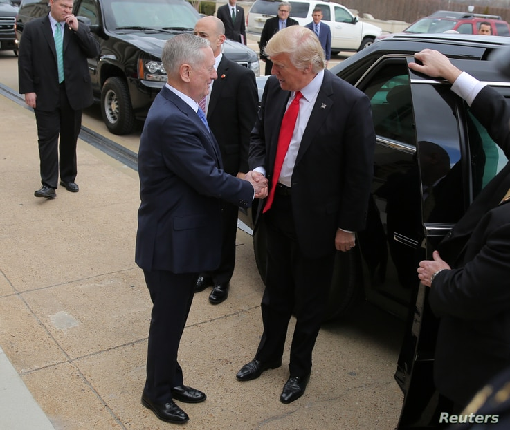 U.S. President Donald Trump is greeted by Defense Secretary James Mattis (L) prior to a swearing-in ceremony for Mattis at the Pentagon in Washington, Jan. 27, 2017.