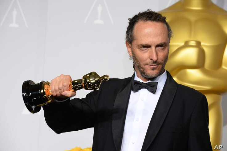 """Emmanuel Lubezki poses in the press room with the award for best cinematographer of the year for """"Gravity"""" during the Oscars."""