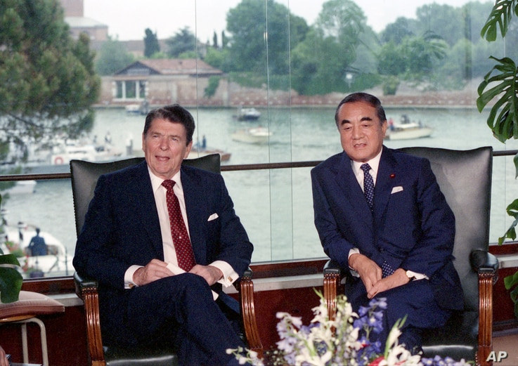 FILE - American President Ronald Reagand, left, and Japanese Prime Minister Yasuhiro Nakasone during their meeting at the Cipriani Hotel, in Venice, Italy, June 8, 1987.