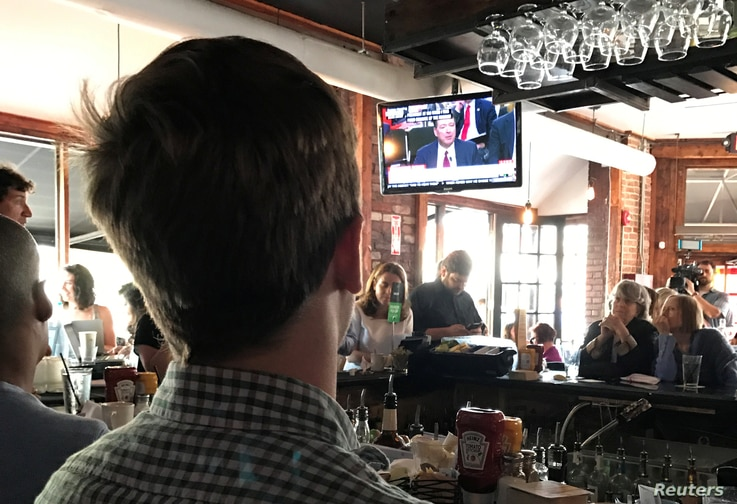 People gather to watch former FBI director James Comey testify before the Senate Intelligence committee in Shaw's Tavern in Washington, June 8, 2017.