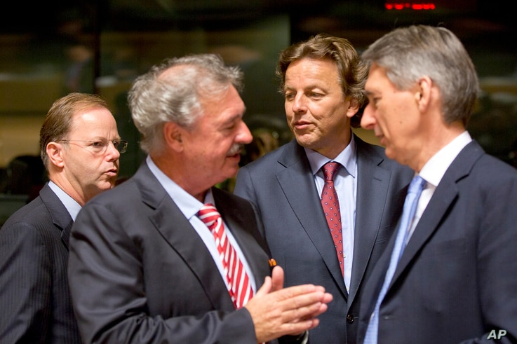 Dutch Foreign Minister Bert Koenders, center, speaks with Luxembourg's Foreign Minister Jean Asselborn, second left, and British Foreign Minister Philip Hammond, right, during a round table meeting of EU foreign ministers in Luxembourg on Monday, Oct...