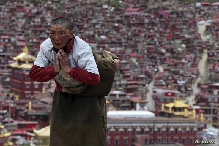 FILE - A Tibetan pilgrim prays near a Buddhist temple in Serthar County, Ganze Tibetan Autonomous Region, Sichuan province, China, July 20, 2015. The academy was founded in the 1980s among the mountains of the remote prefecture.
