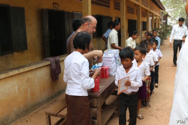 Im Chaem hands out gifts like books, pen and study tools to students during a donation events with US Christian missionary team in November 2017 near her home in O'Angre village, Anlong Veng district, Oddar Meanchey province. Photo by Pastor Touch Ch...
