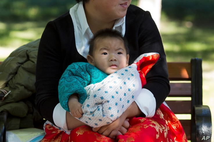 A child is wrapped up against the cold at a park in Beijing, China, Oct. 30, 2015.  Shares of companies making diapers, baby strollers and infant formula got a boost Friday from China's decision to scrap its one-child policy.