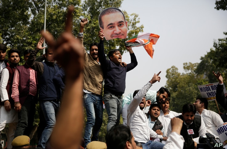 Activists of India's opposition Congress party's youth wing shout slogans against the ruling Bharatiya Janata Party (BJP) as one of them holds a head from a cut out photograph of billionaire jeweler Nirav Modi in New Delhi, India, Feb. 16, 2018.