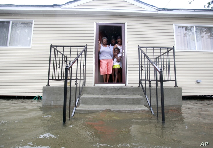 (from L to R) Lessie Lewis, Devin Lewis, Kodi Lewis and Cindy Lewis stand on the front porch as flood waters surround their home on St. Roch ave. as Hurricane Isaac makes land fall in New Orleans, Louisiana August 29, 2012.