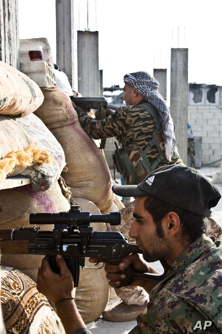 FILE - Kurdish People's Protection Units (YPG)  fighters take position at a stronghold in Kobani, Syria.