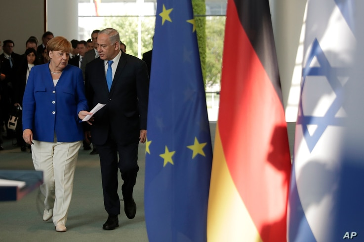 German Chancellor Angela Merkel, left, and and Israeli Prime Minister Benjamin Netanyahu arrive for a news conference after a meeting in Berlin, Monday, June 4, 2018.