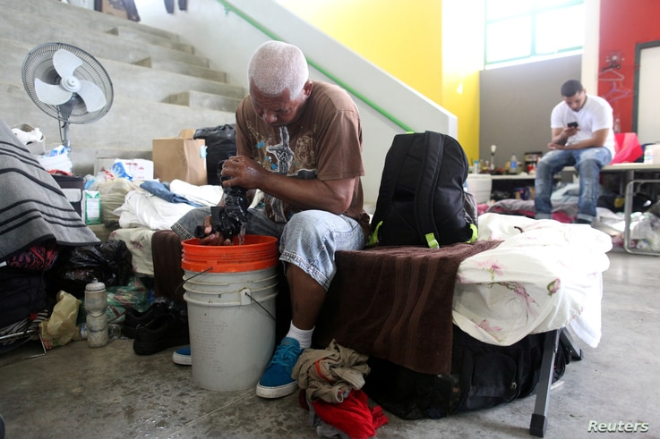 A man does his laundry while sitting on a cot at a school turned shelter after he lost his home during Hurricane Maria in September as former U.S. President Bill Clinton visits Canovanas, Puerto Rico, Nov. 20, 2017.