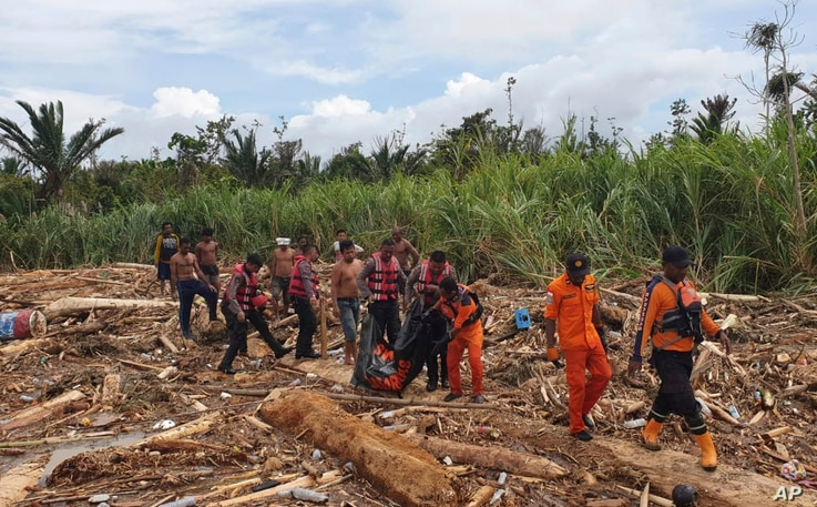 In this photo provided by National Search and Rescue Agency, the agency's personnel and police carry the body of flood victim at Sentani, Papua Province, Indonesia, March 17, 2019.